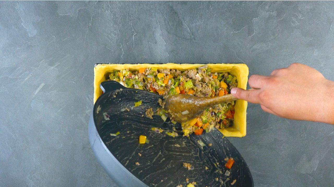 Pasta frolla salata nello stampo a cassetta riempita con la carne macinata e le verdure in padella