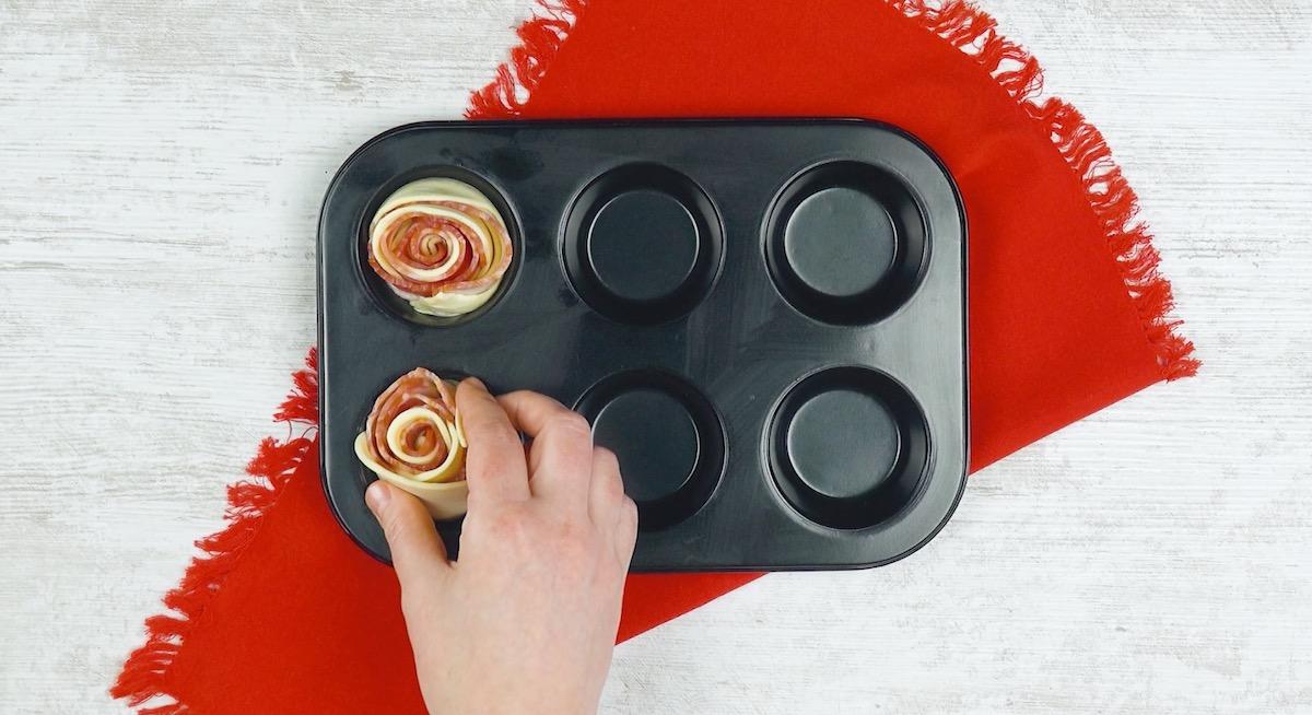 Roselline di pasta sfoglia e pancetta tesa nello stampo per muffin