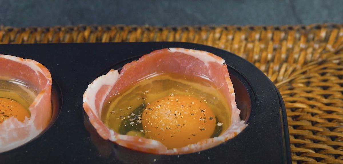 Pancetta tesa e uovo nello stampo per muffin