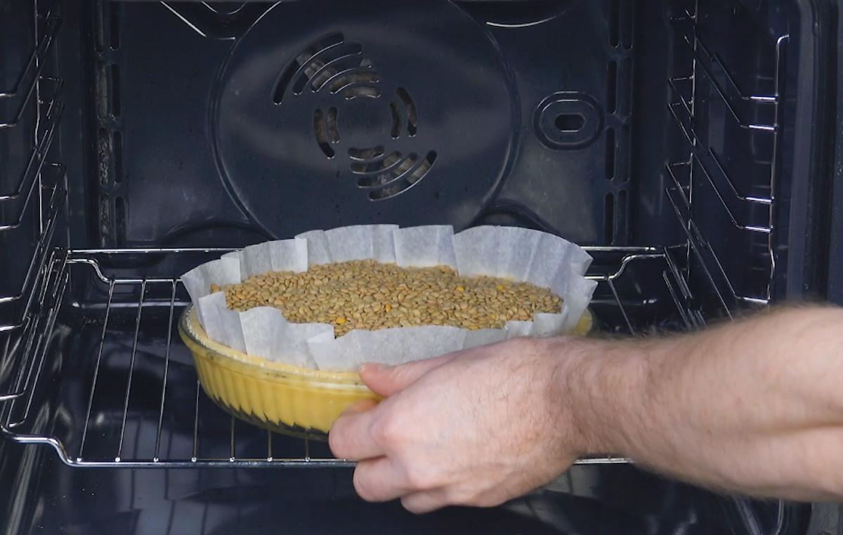 Stampo per crostate con carta da forno e legumi secchi