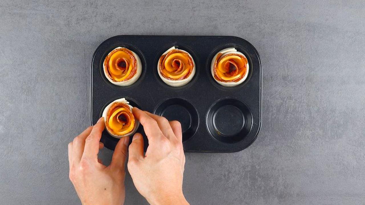 Roselline di pasta sfoglia ripiena nello stampo per muffin