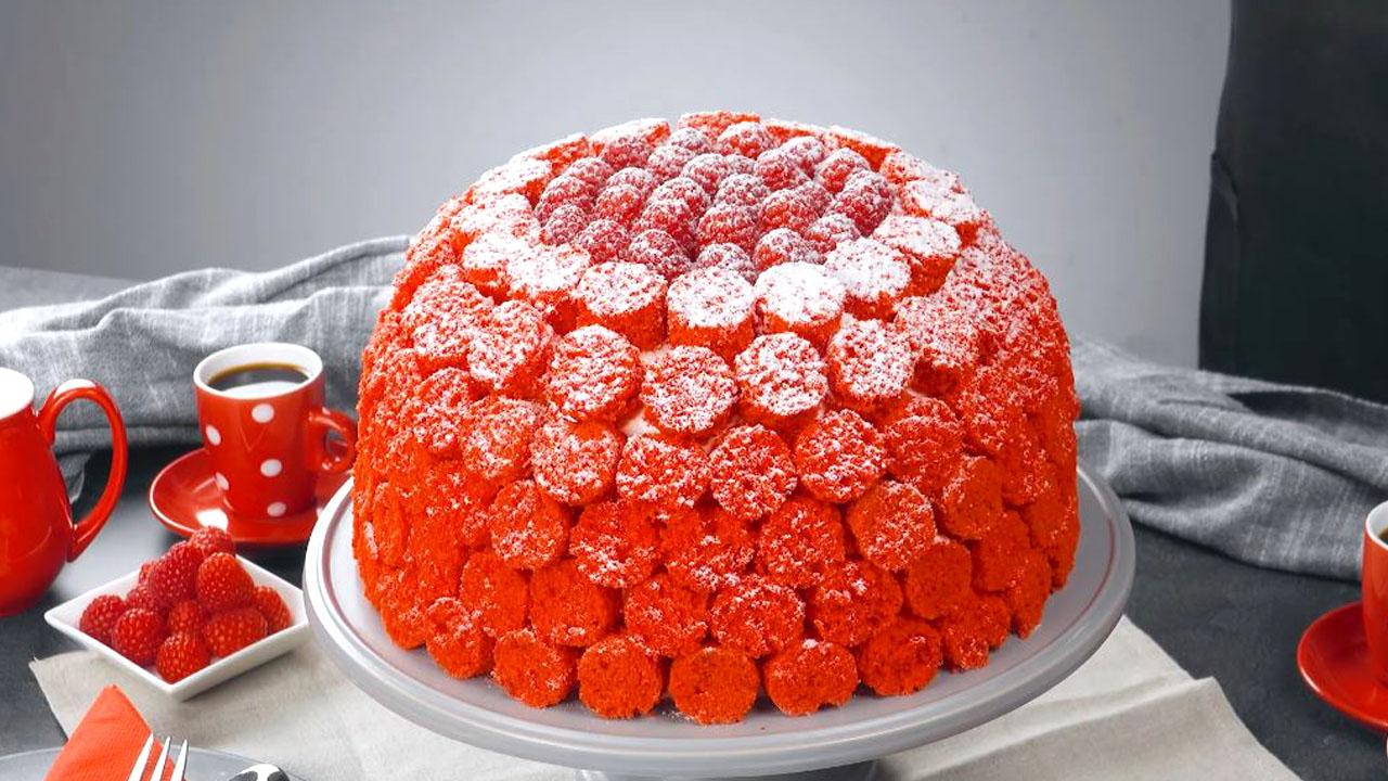 Torta alla frutta di pan di Spagna e crema con panna a forma di grande lampone rosso