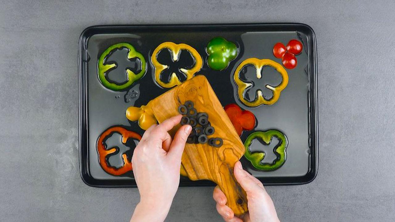 Fette di peperoni e olive nere in teglia