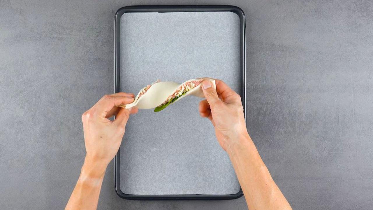 Rustici di pasta sfoglia ripiena di mozzarella per pizza, spinaci e salsiccia