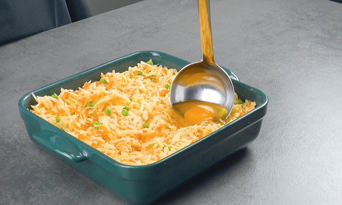 Uovo crudo nel mestolo sullo sformato di verdure