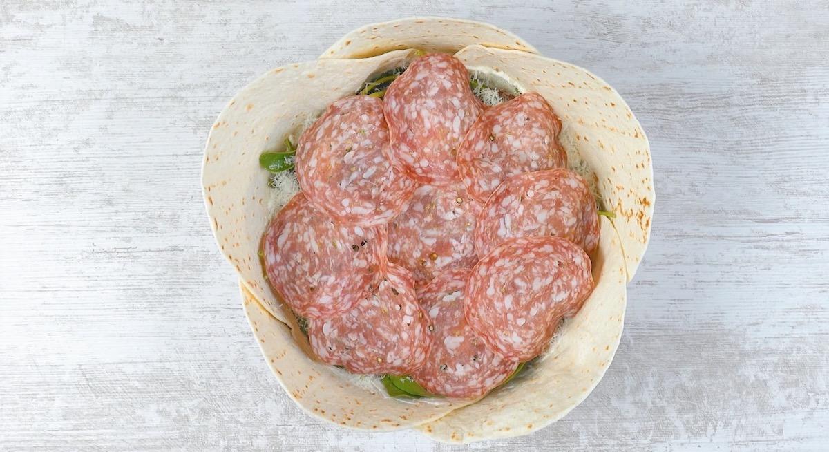 Piadine ripiene di formaggio spalmabile, fette di pomodoro, spinaci novelli, parmigiano e fette grandi di salame
