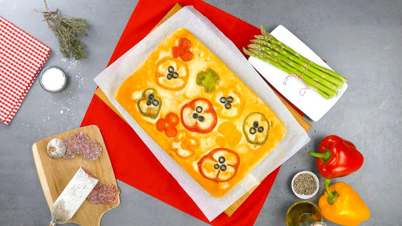 Focaccia condita con peperoni e olive nere