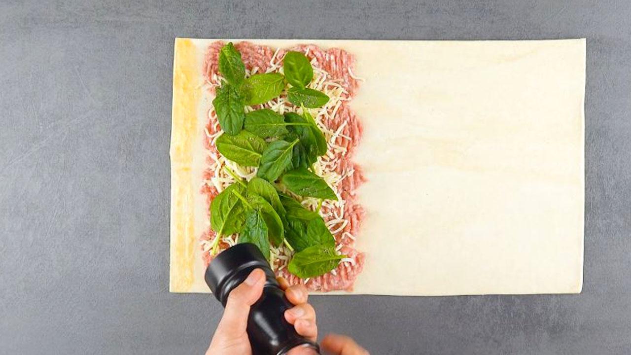 Pasta sfoglia ripiena di mozzarella per pizza, spinaci e salsiccia