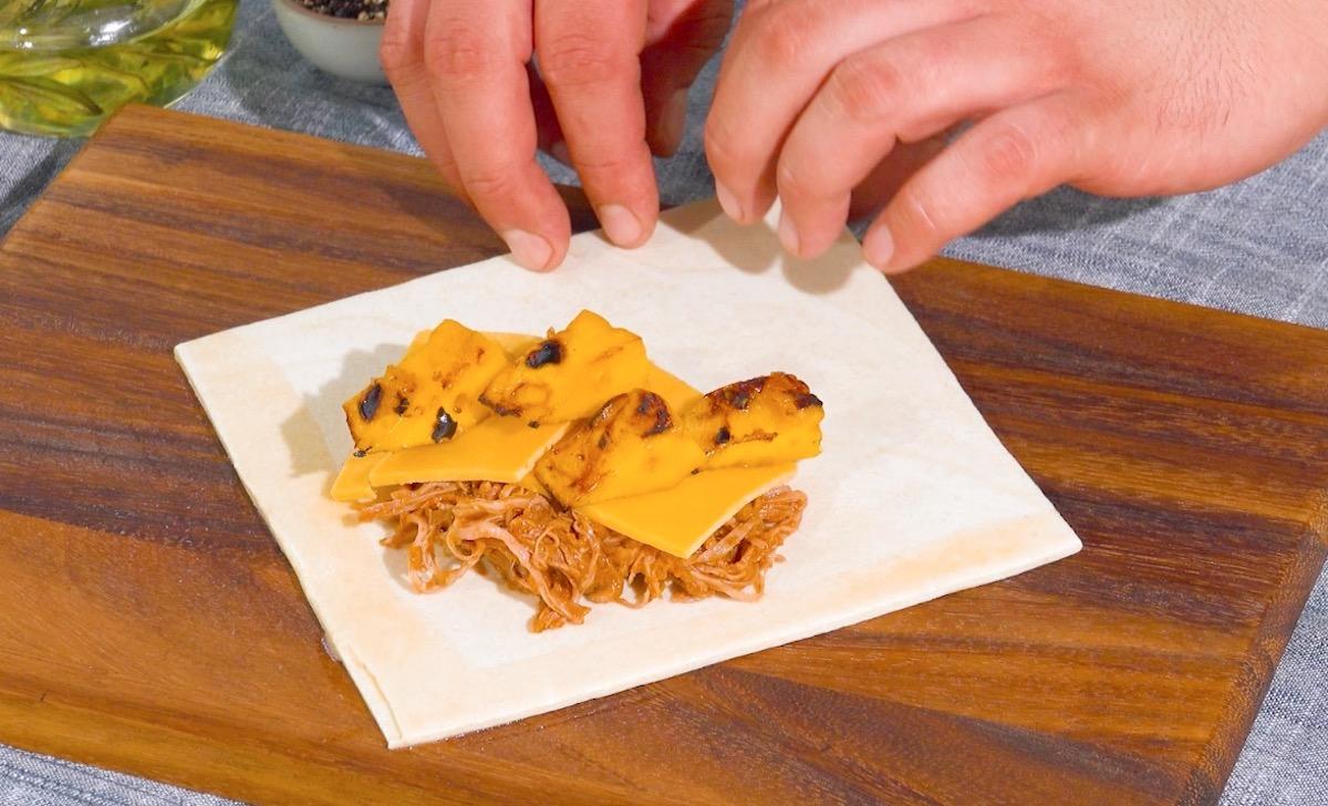 Pasta sfoglia con straccetti di pollo, formaggio cheddar e pezzi di frutta alla griglia